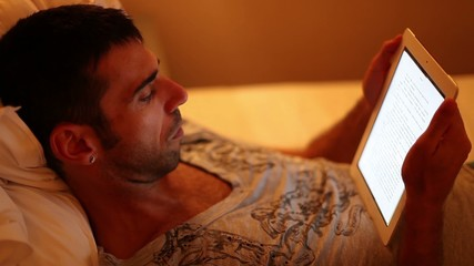 Man reading on his tablet lie on a bed