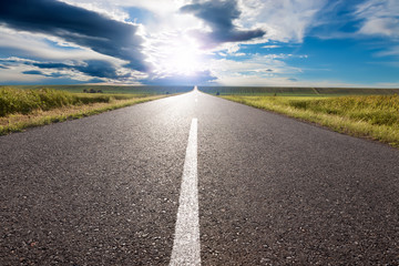 Driving on empty road towards the sun