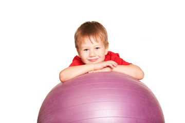 Happy little boy with fitness ball.