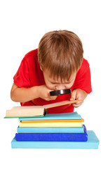 Little boy wearing glasses reading a book with a magnifying glas