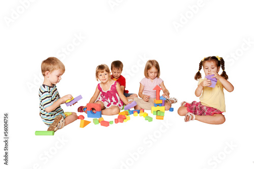 Group of five little children playing and building