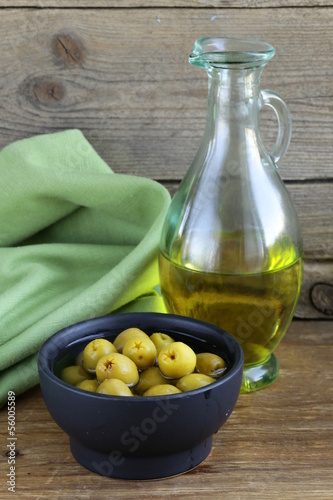marinated green olives and a bottle of oil on wooden table
