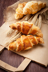 Croissants with spikelets of wheat on a paper bag