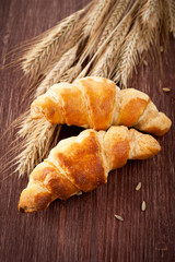 Croissants with spikelets of wheat on the wooden background
