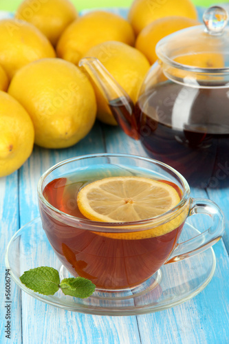 Cup of tea with lemon on table on blue background