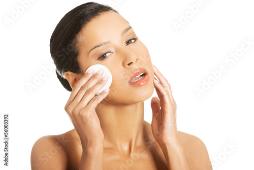 Portrait of happy young woman cleaning skin by cotton pad