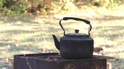 Black old smoked teapot on the campfire