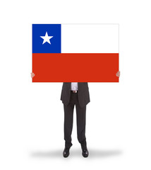 Businessman holding a big card, flag of Chile