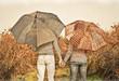 Young couple under an umbrella on the autumn rain.