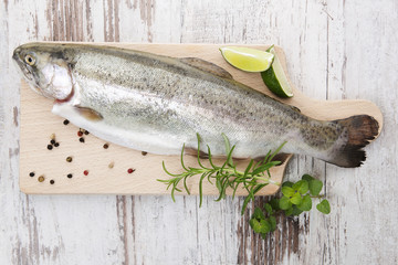 Trout on wooden kitchen board.