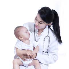 Adorable doctor with a baby in her arms - isolated