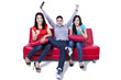 Three young friends cheering at television