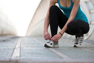 girl lacing her shoes before running outdoors - closeup