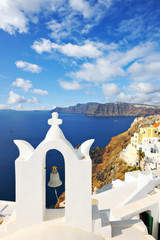 White bell tower overlooking the sea in Oia