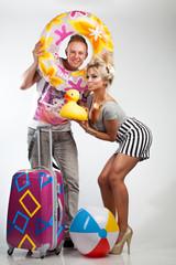 Junges Paar mit Koffer und Urlaubsutensilien