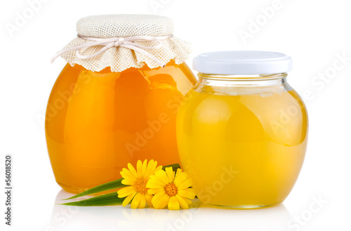 Sweet honey in glass jars with flowers isolated on white