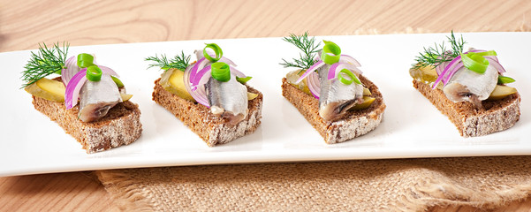 Sandwiches of rye bread with herring, onions and herbs.