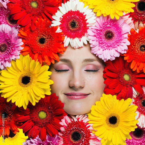 Happy beautiful girl with flowers around her face. Beauty woman