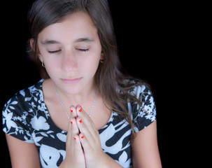 Cute girl praying with her eyes closedisolated on black