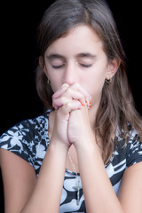 Cute latin girl praying with her eyes closed isolated on black