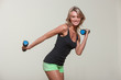 Young athletic blonde woman doing exercises with dumbbells