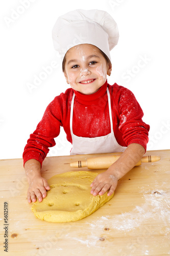 Smiling girl kneading the dough