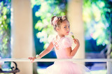 Little ballerina girl doing ballet bar exercises