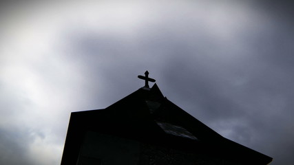 Sinister vision of a cross atop the church in cloudy day