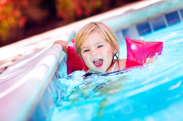 Cute happy baby girl learning swimming with inflatable armbands