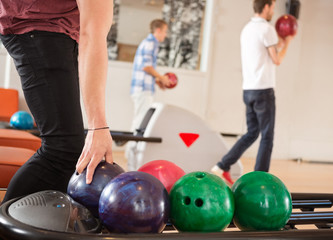 Man Picking Bowling Ball With Friends in Background
