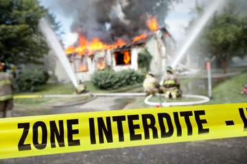 French Zone Interdite tape with firefighters and a burning house