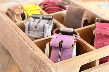 Set of stylish vintage belts in wooden crate