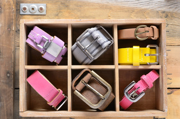Collection of stylish belts in wooden crate