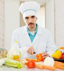 caucasian cook cuts red pepper
