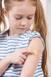 Vaccination. Cheerful little girl holding finger on the arm