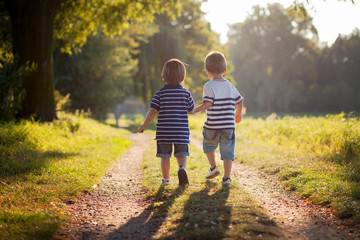 Two boys, walking in a park
