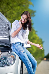Beautiful woman with car trouble talking over a phone