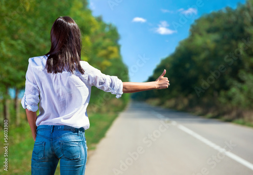 Woman hitchhiking back view