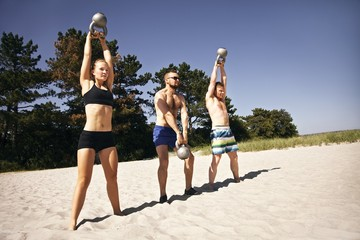Group of athletes working out with kettle bell on beach