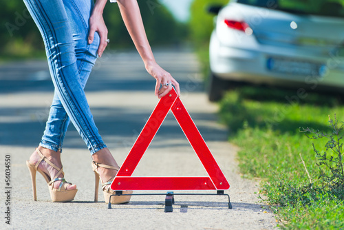 Woman putting a triangle on a road,car trouble
