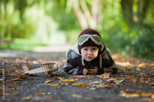 Boy in a park, playing with a plane