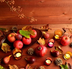 Autumn fruits with candle.brown wood background