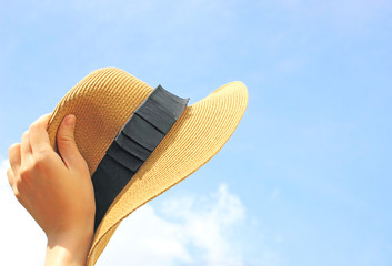 Woman hand holding panama hat with blue sky