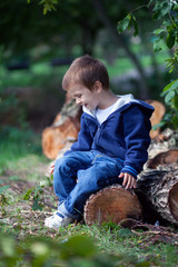 Boy, sitting on a wooden trunk