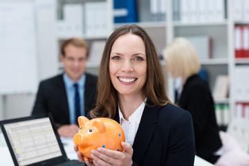lächelnde angestellte hält sparschwein in händen