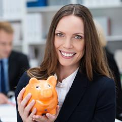 freundliche geschäftsfrau mit orangem sparschwein