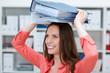 lächelnde geschäftsfrau trägt akten auf ihrem kopf