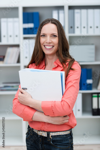 lächelnde frau im büro mit aktenordner