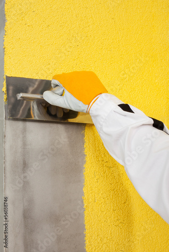 A trowel spreading a plaster on a corner-wall