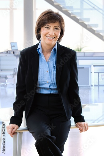 Happy mature businesswoman in office